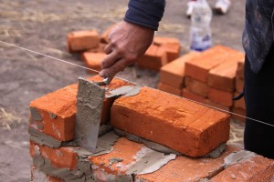 Man building brick wall